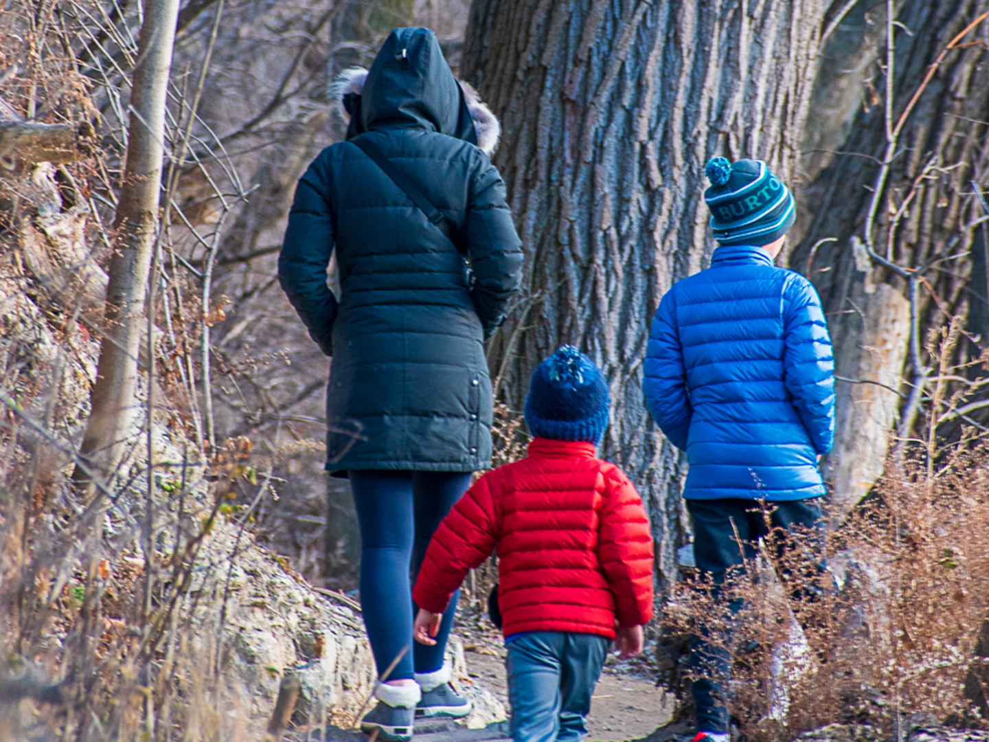 A woman and two boys walk along the Milwaukee River at Estabrook Park