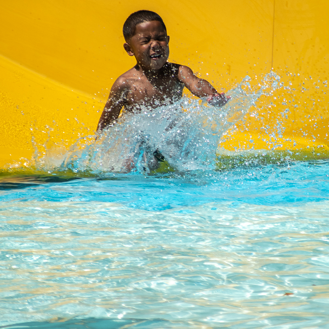 Child splashing into a pool from a water slide